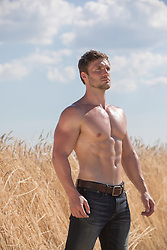 shirtless muscular man by a field