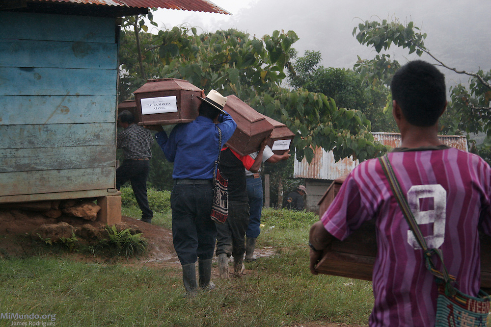 Men carry the remains of 14 wartime Ixil Mayan victims to be returned to their families. The National Coordination for Guatemalan Widows (CONAVIGUA) and the Forensic Anthropological Foundation of Guatemala (FAFG) returned the remains of to their respective family members in the hamlet of Xaxmoxan, Chajul, up in the Ixil Mayan highlands of Quiché, after successful exhumations of clandestine mass graves. Most of the victims perished in the mountainside between 1980 and 1983 as they fled the Army's brutal Scorched Earth campaign against a civil population accused of supporting the guerrilla groups in the region. Xaxmoxan, Chajul, Quiché, Guatemala. January 25, 2007.