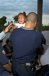 29 August, 2005. New Orleans, Louisiana.<br /> Hurricane Katrina hits New Orleans. Rescue workers collect Faith Figueroa (1yrs), saved by local police and firefighters from her family's flooded home in the lower 9th ward.<br /> Photo; Charlie Varley.