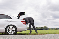 Side view of young businessman looking in trunk of car at countryside