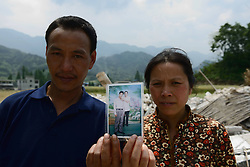59601372 .The 43-year-old Zeng Youkang (L) and his 40-year-old wife Luo Congqiong pose for photo with an old picture in the quake-hit Longmen Village, southwest China s Sichuan Province, May 4, 2013. The old picture was taken in 2002 in east China s Changzhou city. Old photos are not daily necessities for who just suffered a 7-magnitude earthquake, but they are still cherished as they recorded peoples past life and recalled memories, May 4, 2013.  Photo by: i-Images.UK ONLY