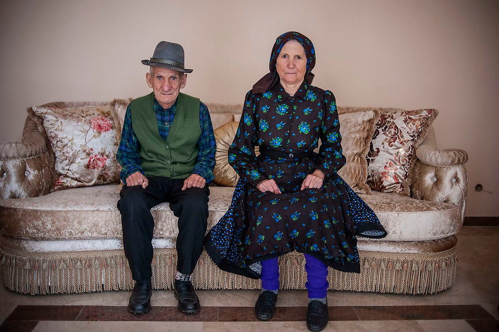 Gheorghe and Maria Balta sit on a sofa in a new home being built by their children who all work in Paris. They have extended and enlarged the old house into a much larger building which now has two floors and a glass front.