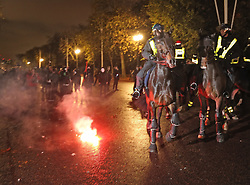 © Licensed to London News Pictures. 05/11/2015. London, UK. Mounted police have trouble controlling their mounts in The Mall near Buckingham Palace as anti-capitalist protestors throw a flare during the Million Mask march. Photo credit: Peter Macdiarmid/LNP