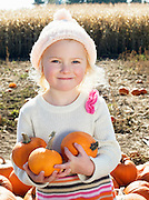 Portrait of a happy girl holding pumpkins in farm