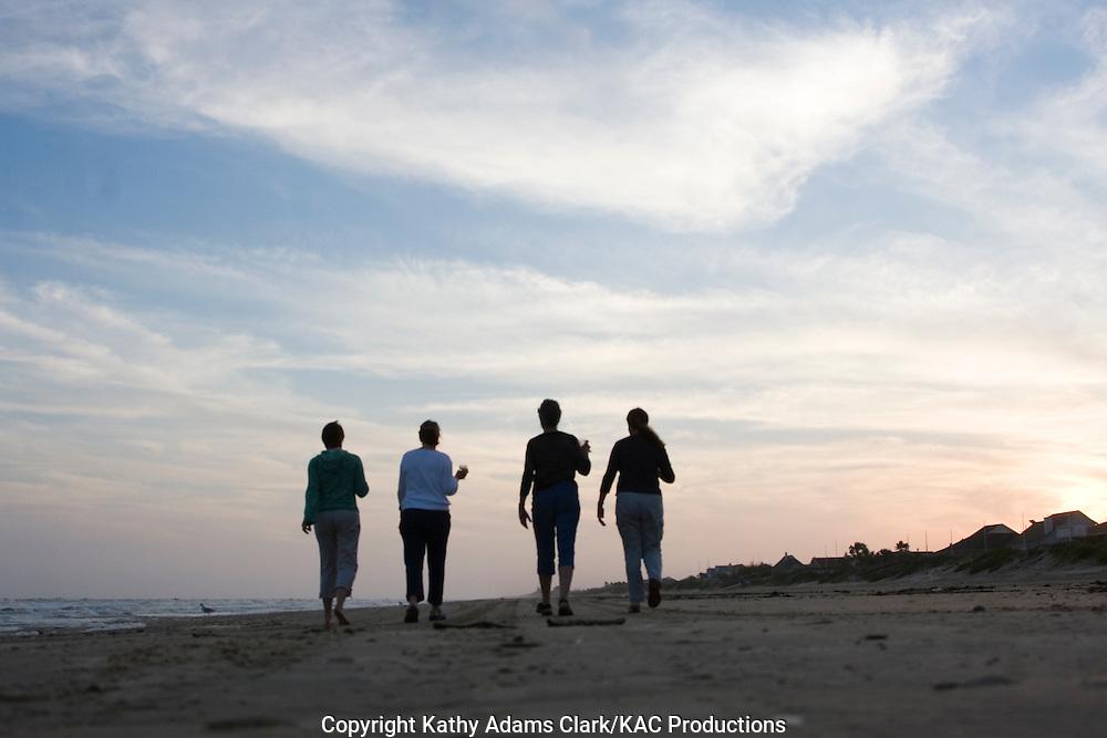 four women walking on beach at sunset, Galveston, Texas.  Silhouette.