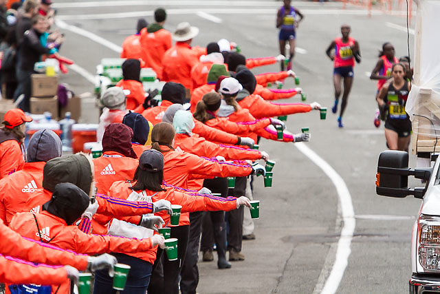 volunteers hold cups of water for runners