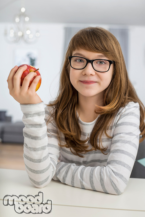 Portrait of teenage girl holding apple while sitting at table in house