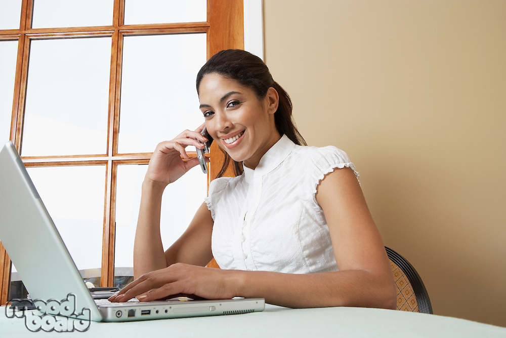Business woman using mobile phone at desk in office, portrait