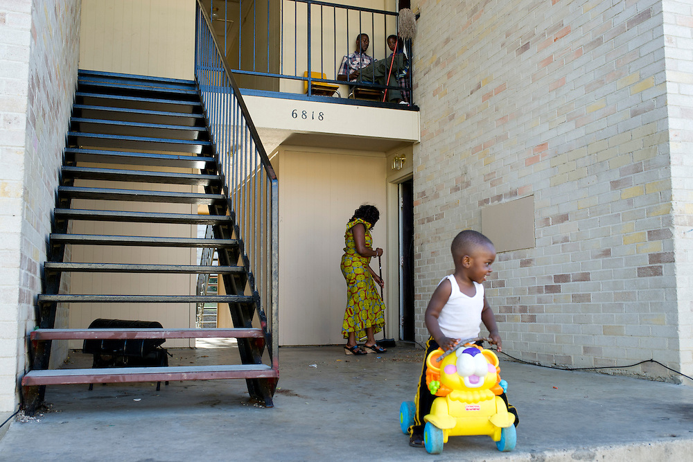 Estella Ndayikunda sweeps outside her apartment at ParkLane Terrace with her son Fledson, 2, in Dallas, Texas on October 5, 2014. Ndayikunda lives in the unit directly below Youngor Jallah, who along with her family, have been quarantined and monitored daily for symptoms of Ebola. (Cooper Neill for The New York Times)