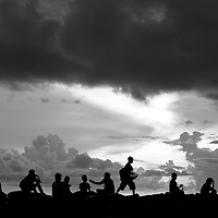 Where - Madura island, Indonesia. A boy sells his goods to locals at sunset.