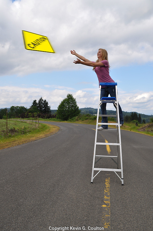 "Humorous photograph of a woman throwing a CAUTION warning sign into the air visually depicting the saying ""Throw caution to the wind""."