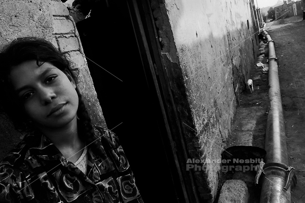 Cairo, Egypt, The City of the Dead, 2000 - Teenage girl outside her home next to the temporary water main.