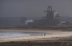 © Licensed to London News Pictures. <br /> 01/02/2015. <br /> <br /> South Gare, Redcar, United Kingdom<br /> <br /> A man walks his dogs on a windswept beach in the shadow of the steel works at the mouth of the Tees at South Gare near Redcar in Teesside.<br /> <br /> Photo credit : Ian Forsyth/LNP