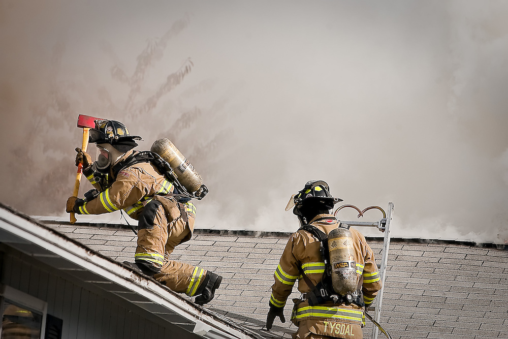 JEROME A. POLLOS/Press..Coeur d'Alene firefighter Luke Pichette sounds a roof for safety before cutting holes in it to ventilate a house fire Monday on Howard Street.