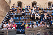 "Italy, Siena, the Palio: If you want to see the Palio you can choose among the wooden Seats called ""Palchi"" (all around the square), the windows of the Palaces on the Square and the balconies. The last are very few and, as they have a higher position and better view, like the windows,  they are more expensive. The balconies can accommodate up 2 rows of people (the first have chairs the second just stand). The windows are managed directly by the owners of the Palaces in the Campo Square or by the same Palio Business Men."