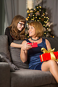 Daughter giving Christmas present to mother at home