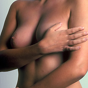 Studio female nude, hand covering one breast while exposing the other breast