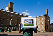 A member of the prison art club holds up one of his paintings. HMP Wandsworth, London, United Kingdom