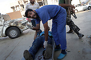23 August 2011. A doctor rescue a wounded rebel during the battle in Bab Al Azizia the main stronghold of Gheddafi.