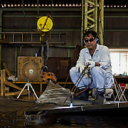 Worker bending an iron plate at Tsuneishi Iron Works, a part of Tsuneishi Holdings that prepares ship pieces that will be used at Tsuneishi shipbuilding. Complicated shapes of the iron plates can not be created by machines so workers have to work on each piece for up to 15 hours to give it the right shape. Because of the very high summer temperatures at the factory he has removed the safety helmet that all workers are required to wear at all times.