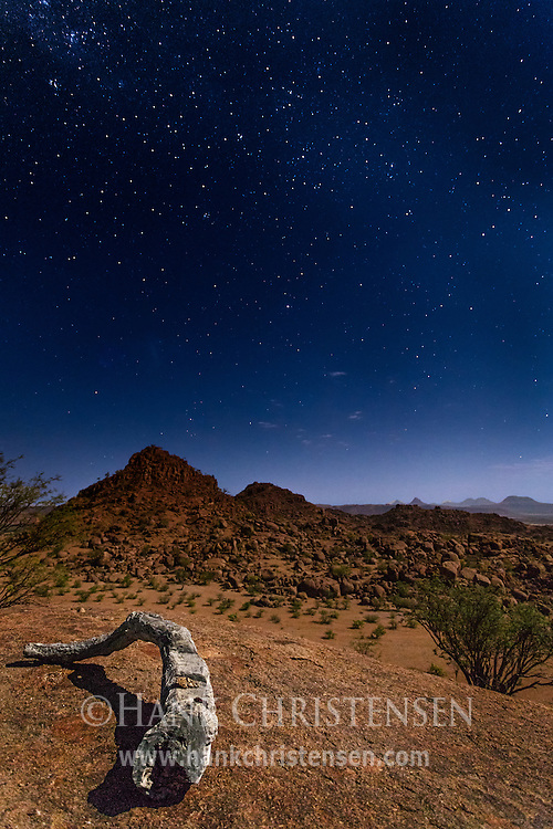 Stars light the night sky over the desert landscape of Damaraland, Twyfelfontein, Namibia.