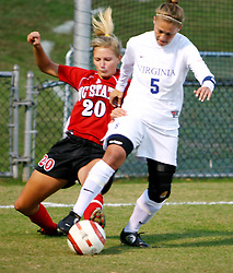 UVA midfielder Shannon Foley (#5) protects the ball from a tackle by NC State's Megan Buescher.  UVA won the match 2-0.