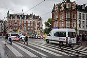 Voetgangers en auto's vinden hun weg op het drukke Muntplein in Amsterdam. Een verkeersregelaar houdt een taxibusje tegen, een politiewagen wacht bij het zebrapad tot een vrouw met een blindegeleidestok is overgestoken.<br /> <br /> Traffic at the Munt Square in Amsterdam. Traffic controlers stop a taxi van, while a police car waits for a blind woman to cross the street.