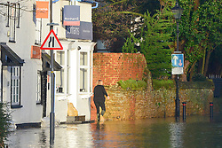 © Licensed to London News Pictures. 03/01/2014. Guildford, UK A woman walks through the floodwater. Guilford town centre River Wey bursting it's banks in Surrey today 3rd January 2013. Floods an heavy rain are continuing to effect travel and people across the country today. Photo credit : Stephen Simpson/LNP