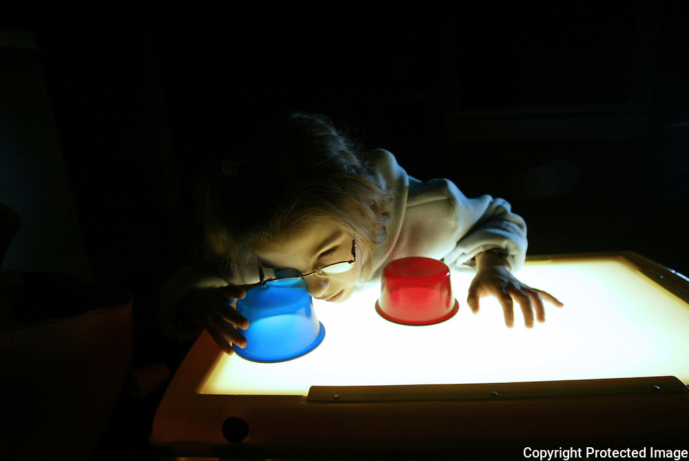 Annabelle Costanzo attempts to distinguish colors as she looks through translucent cups on a light table at her home in Des Moines, Iowa.  Annabelle had just returned home from Detroit where she had another procedure done to try to restore her sight.