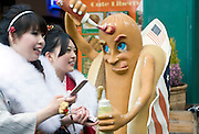 Kimono-clad 20-year-old Japanese women walk past a store selling hot-dogs as they make their way to an event to mark Coming-of-Age Day in Tokyo, Japan on Monday Jan. 11, 2009. Japanese enter adulthood at 20, when they can legally smoke, drink alcohol and vote, though debate is heating up as to whether or not the age should be lowered to 18 in line with many advanced countries. Indeed, the Japanese government plans to lower the voting age to 18 as of mid-2010.   .Photographer: Robert GilhoolyCOMING OF AGE