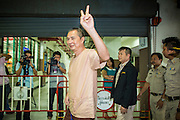 "23 JANUARY 2013 - BANGKOK, THAILAND:   SOMYOT PRUESAKASEMUK waves the ""V for Victory"" as he walks into Bangkok Criminal Court followed by court security Wednesday. Somyot was sentenced to 11 years imprisonment Wednesday for violations of Thailand's ""Lese Majeste"" laws. He was arrested on April 30, 2011, and charged under article 112 of Thailand's penal code, which states that ?whoever defames, insults or threatens the King, the Queen, the Heir-apparent or the Regent, shall be punished with imprisonment of three to fifteen years"" after the magazine he edited, ""Red Power"" (later changed to ""The Voice of Thaksin"") published two articles by Jit Pollachan, the pseudonym of Jakrapob Penkair, the exiled former spokesman of exiled fugitive former Prime Minister Thaksin Shinawatra. Jakrapob, now living in Cambodia, has never been charged with any crime for what he wrote.     PHOTO BY JACK KURTZ"