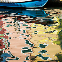 Colorful reflrctions of buildings on the canals of the island of Burano, Italy.