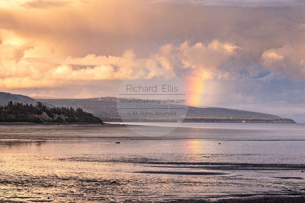 A rainbow breaks through storm clouds over Beluga Slough on the Kachemak Bay in Homer, Alaska.