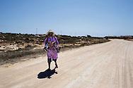 Lampedusa, Italia -  3 luglio 2011. Un venditore ambulante cammina in cerca di clienti su una strada generalmente battuta dai turisti sull'isola di Lampedusa. Anche i venditori ambulanti hanno subito un netto calo delle vendite dovuto alla mancanza di turisti sull'isola..Ph. Roberto Salomone Ag. Controluce.