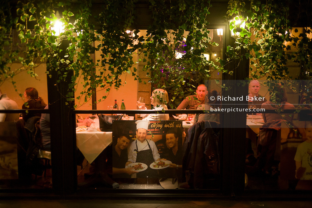 "Tourists enjoy food and drink in an outdoor restaurant tent in Florence, Italy. A photo of the restaurant's chef with possibly two other cooks are seen in a window ad that bears the words ""Enjoy with Us"" - an invitation to come dine with the owners of the pizzeria. Customers are seated under strong lights in this otherwise dark street, enjoying wine and their respective partners' company."