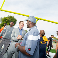 Life Remodeled CEO, facing camera, greets Cody High School football coach Calvin Norman while celebrating the school's new field.