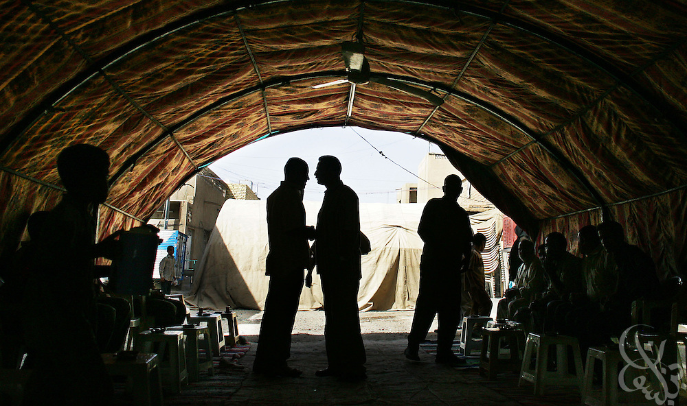 Relatives of slain Shia university student Zainub Kareem, age 26, gather under a traditional mourning tent in the Sadr city neighborhood of Baghdad, Iraq June 09, 2006.  Kareem was shot to death by unknown gunmen yesterday, June 08, 2006 along along with 2 of her friends outside their university in Northern Baghdad.