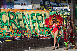 © Licensed to London News Pictures. 28/08/2017. London, UK. Carnival goers walk past a graffiti sign for Grenfell Tower on the second day of the 2017 Notting Hill carnival. The two day event is the second largest street festival in the world after the Rio Carnival in Brazil, attracting over 1 million people to the streets of West London. Photo credit: Ben Cawthra/LNP