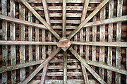 Looking up into rafters of a tiled roof.