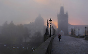 Dawn at the Charles Bridge or Karluv most, built 1357 - 15th century, looking towards the Old Town bridge tower, with the Crucifix and Calvary sculpture, 1657, across the Vltava river in Prague, Czech Republic. Its construction began under King Charles IV, replacing the old Judith Bridge built 1158'??1172 after flood damage in 1342. This new bridge was originally called the Stone Bridge (Kamenny most) or the Prague Bridge (Prazsky most) but has been the Charles Bridge since 1870. The bridge is 621m long and nearly 10m wide, resting on 16 arches shielded by ice guards. It is protected by three bridge towers, two on the Lesser Quarter side and one in Gothic style on the Old Town side. The historic centre of Prague was declared a UNESCO World Heritage Site in 1992. Picture by Manuel Cohen
