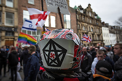 © Licensed to London News Pictures . 28/02/2015 . Newcastle , UK . A man wearing a bike helmet with a swastika inside a pentagon drawn on it at the Pegida demonstration . Hundreds attend the first Pegida demonstration in the UK , at the Bigg Market in Newcastle . Photo credit : Joel Goodman/LNP