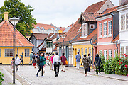 Visitors strolling in Ramsherred cobbled street in old town in Odense on Funen Island, Denmark