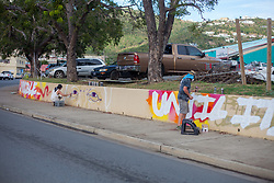 Anthill Collective members Brian Clark, Scottie Raymond, and Jared Mattes spray paint a mural at Mandela Circle.  The mural features a portrait of Nelson Mandela, one of his famous quotes, and scenes of local caretaker Makemba who used to clean and frequent the area.  26 March 2018.  St. Thomas, VI.  © Aisha-Zakiya Boyd