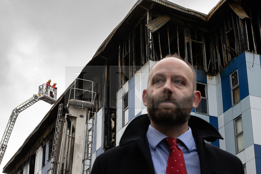 "© Licensed to London News Pictures. 16/11/2019. Bolton, UK. PAUL DENNETT of Greater Manchester's High Rise Taskforce at a the site of the blaze . Firefighters work at the scene where a fire broke out overnight (15th/16th November 2019) at a block of flats known as "" The Cube "" , in Bolton Town Centre . At least two people are known to have been treated by paramedics at the scene of the six-story block , which is occupied by students of the University of Bolton . Photo credit: Joel Goodman/LNP"