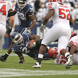 Oct 31, 2009; East Hartford, CT, USA; Connecticut running back Jordan Todman (23) is tackled by Rutgers defensive end George Johnson (31) and linebacker Antonio Lowery (50) during second half Big East NCAA football action in Rutgers' 28-24 victory over Connecticut at Rentschler Field.