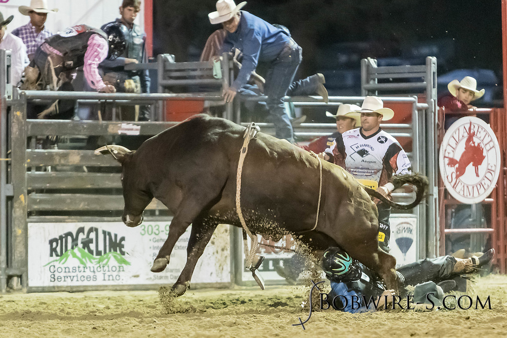 Bullfighters Nate Jestes (in the light shirt) and Cade Burns rescue bull rider Colton Kent from Summit Pro Rodeo's Lady Luck in the second performance of the Elizabeth Stampede on Saturday, June 2, 2018.