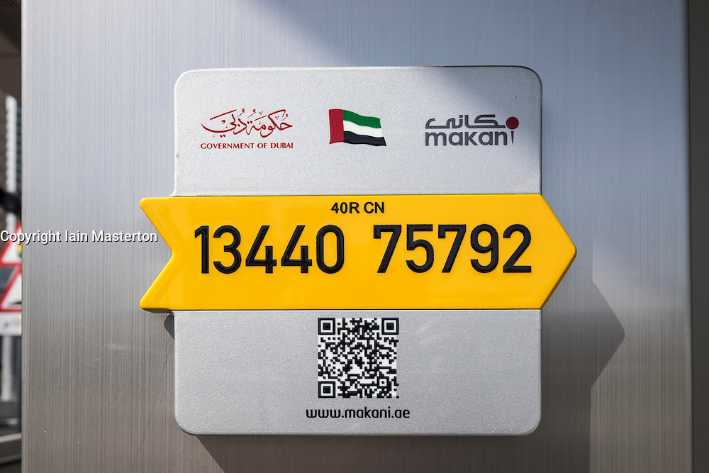 Makani geographic information system (GIS) address location sign with unique 10 digit code attached to building in Dubai United Arab Emirates