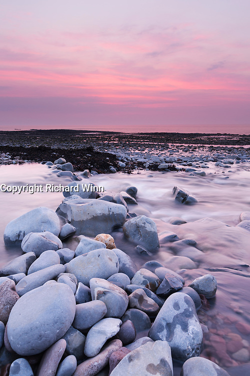 Sunset over the Bristol Channel, viewed from the edge of Kilve Beach, with Kilve Pill in the foreground.