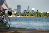 Summer scene as a biker rides along the park trails of Lake Calhoun in Minneapolis, Minnesota.