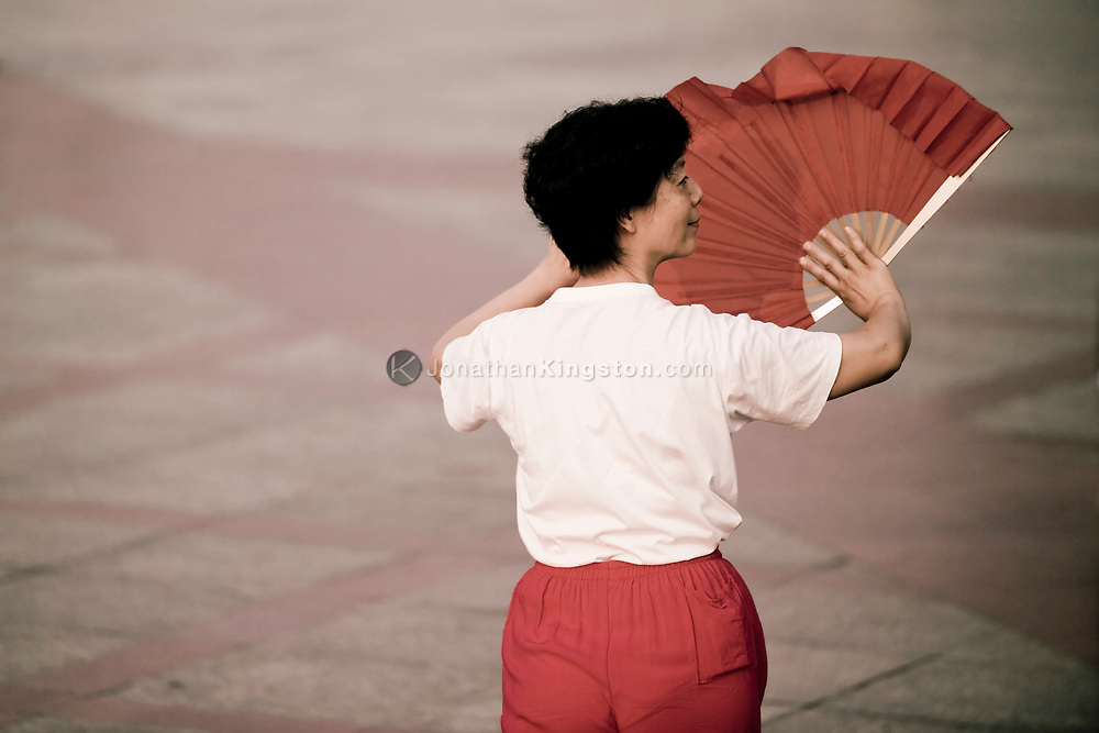 A chinese woman practices Tai Chi with a red fan in the early morning, peoples square, Huangpu district, Shanghai, China.  Shanghai is one of China's most important cultural, commercial, financial, industrial and communications centers.  It is also one of the busiest ports in the world and is a major economic center.